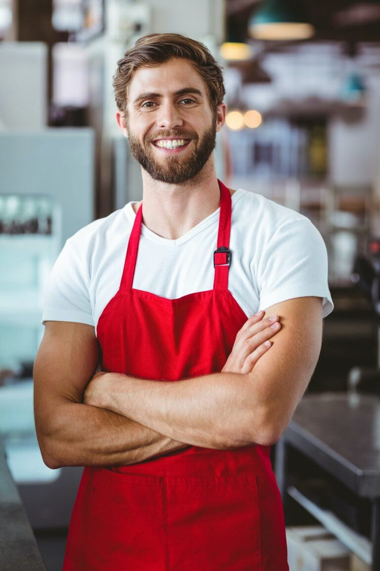 Handsome barista smiling at the camera at the cafe