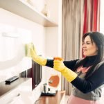 Housemaid cleans furniture with a cleaning spray