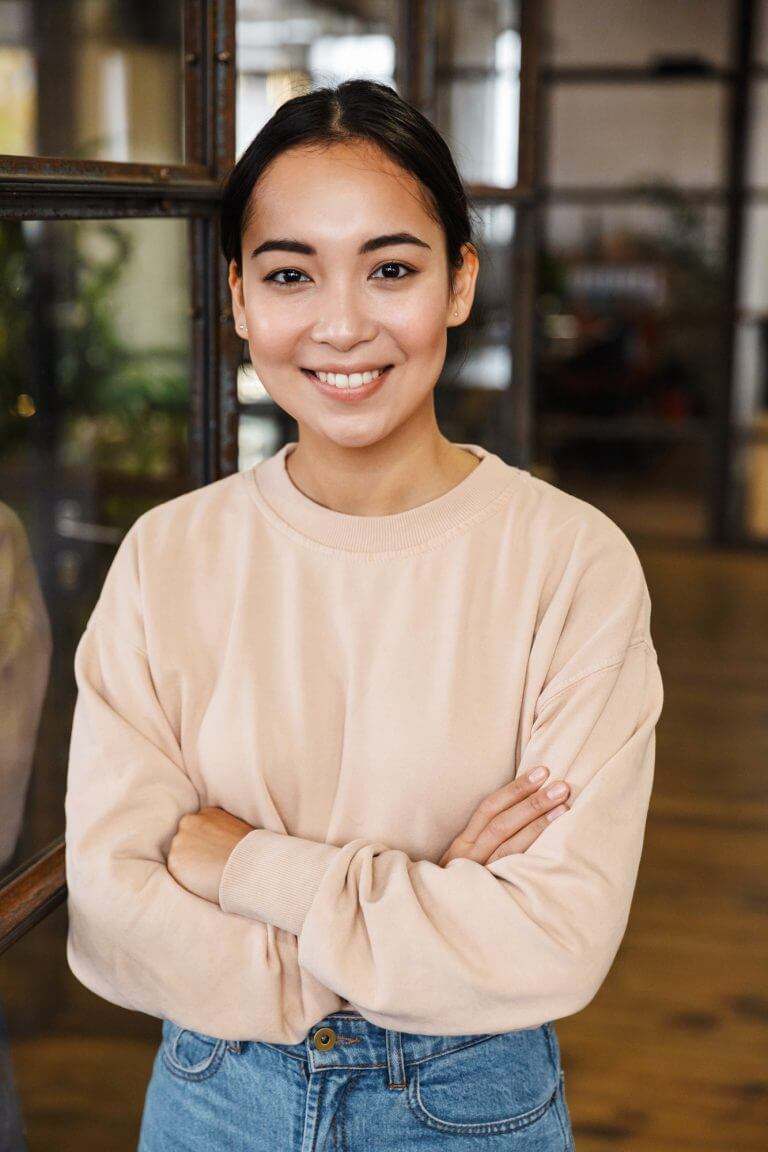 Image of young asian woman smiling and standing with arms crossed