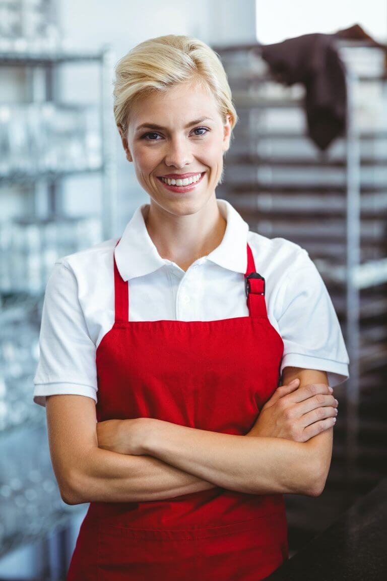 Pretty barista smiling at the camera with arms crossed